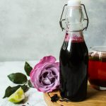 Hibiscus syrup in bottle with rose beside it
