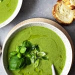 Courgette soup in a bowl with bread on the side