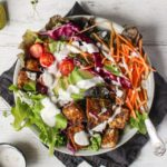 Overhead of jerk tofu salad with salad dressing on top