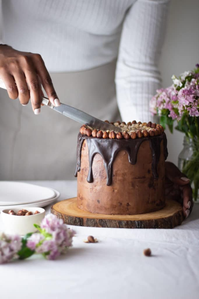 Eye level photo of person cutting cake