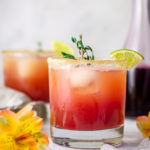 Eye-level photo of rum punch with grenadine in the background