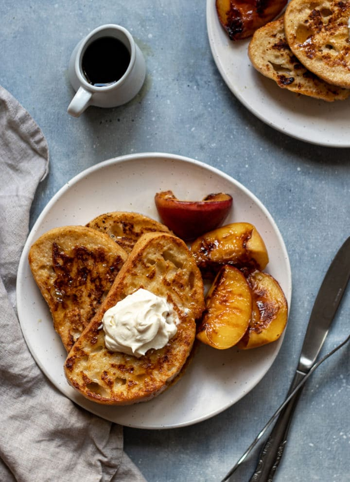 overhead photo of sourdough french toast with grilled peaches, maple syrup and whipped cream